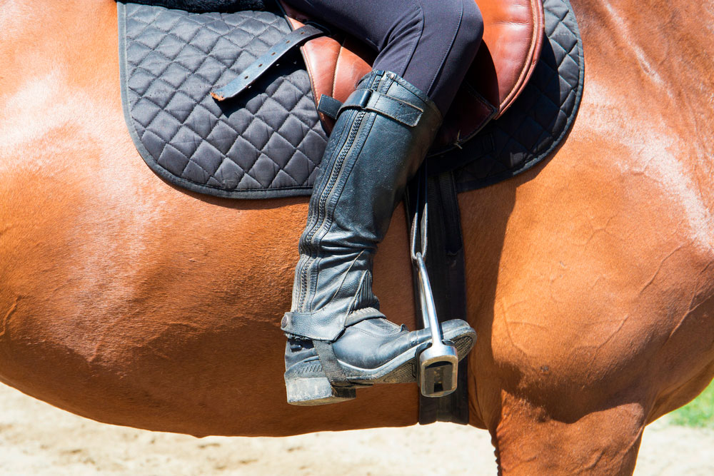 Girl in a saddle with black boots