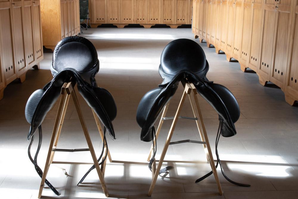 black saddles rest on saddle stands