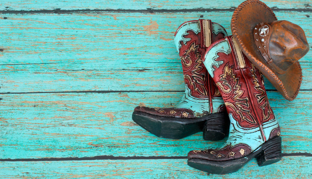 cowboy boots and hat on teal wood