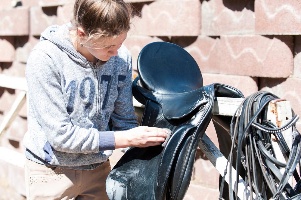 girl cleaning black saddle