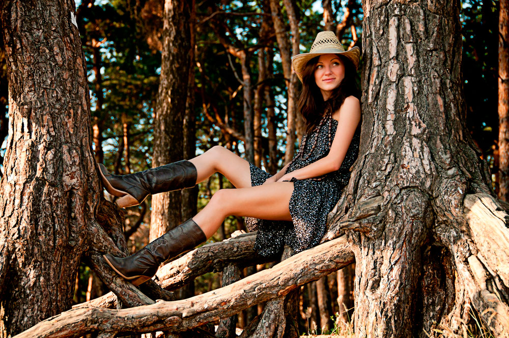 girl in boots posing on tree