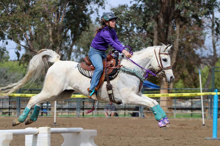 girl jumping on Arabian Horse