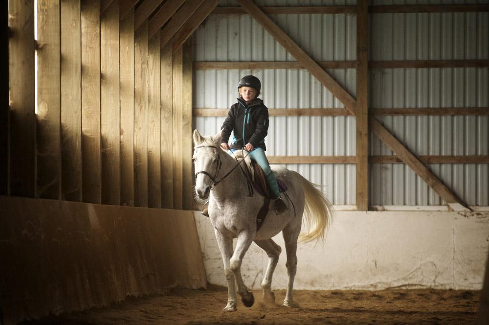 kid in helmet riding horse