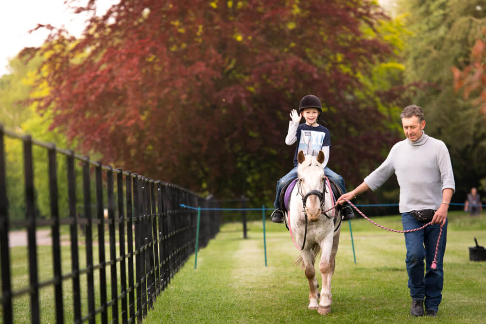 little boy in helmet riding horse