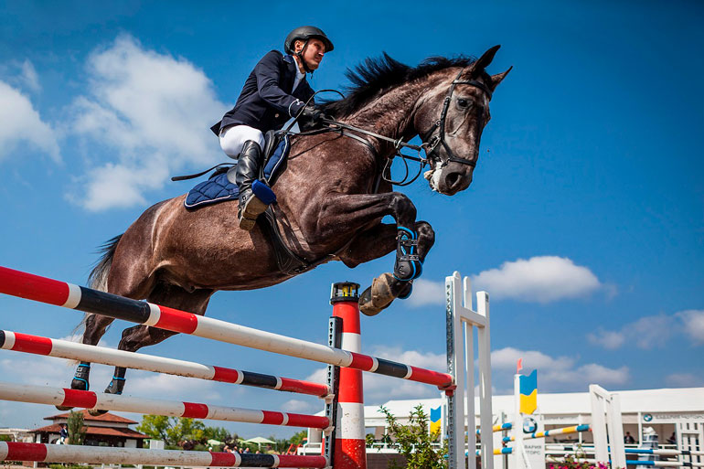 man is jumping over obstacle with horse