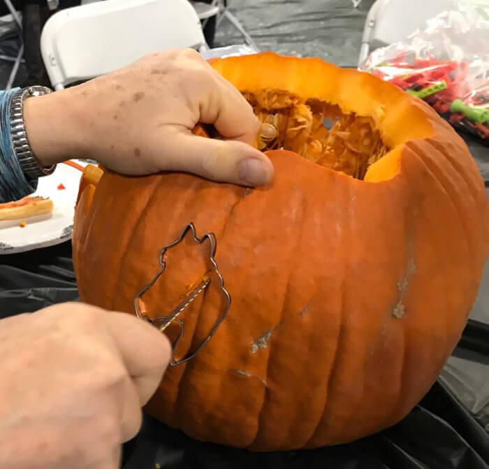 man is using pumpkin carving knife