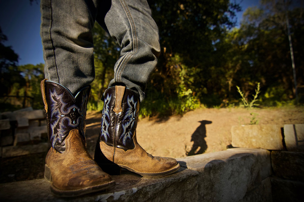 man standing in cowboy boots with stitching