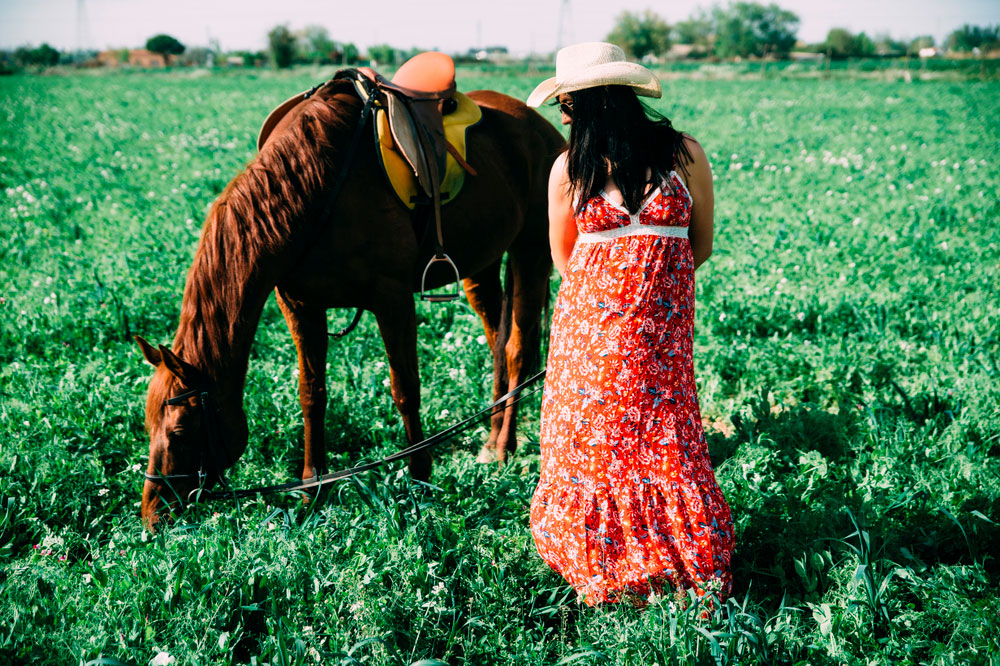 pregnant woman in red standing near horse