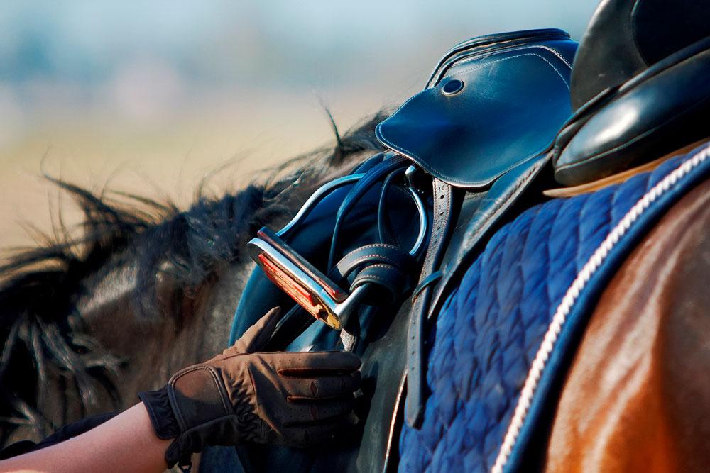 rider checks saddle stirrups