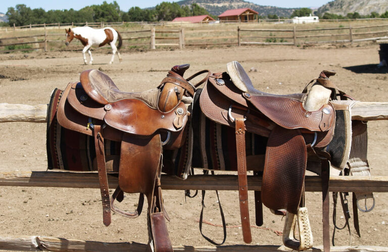 western saddles resting on fence