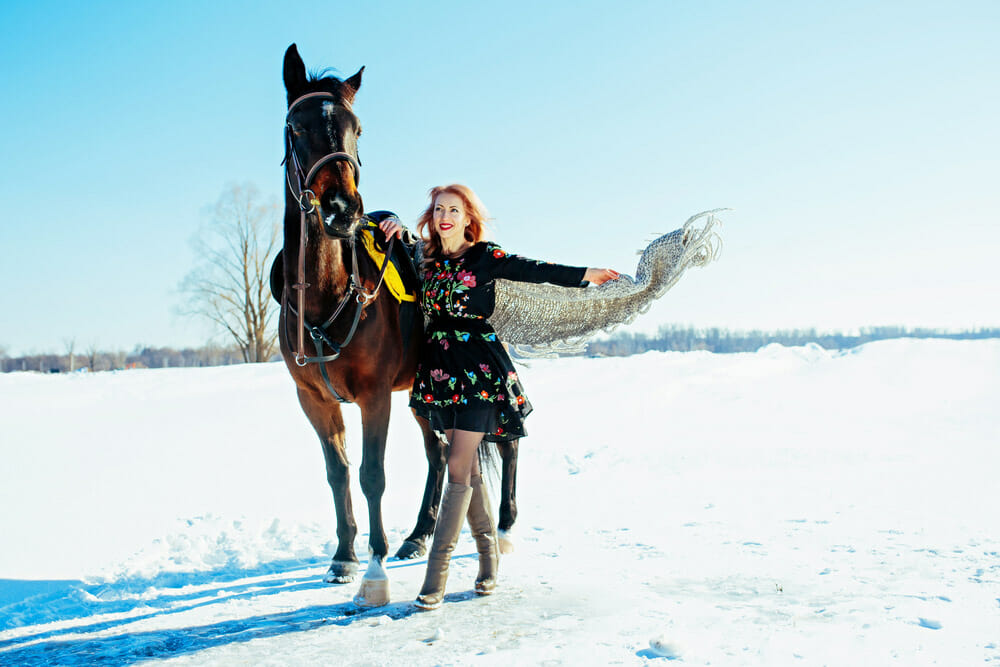 woman in dress is posing with a horse