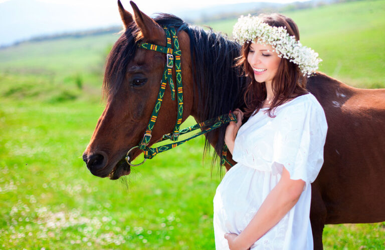 woman in white holding horse