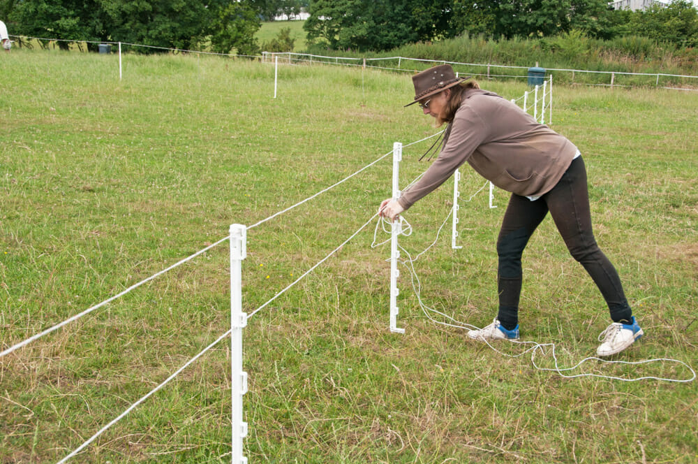 woman is installing an electric fence