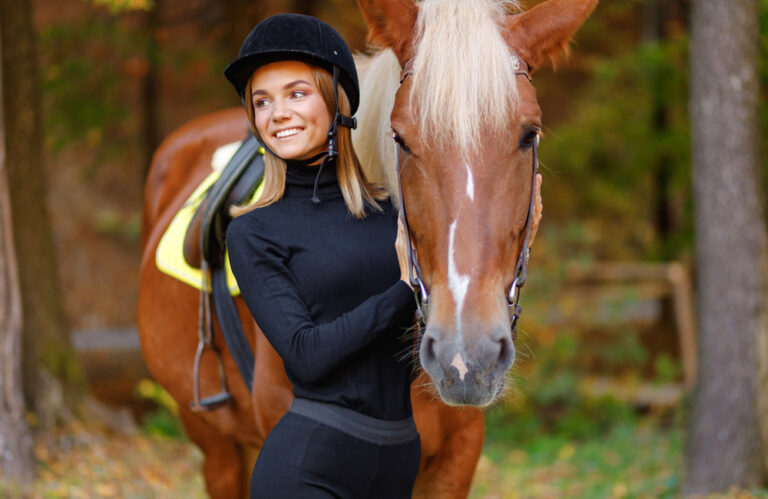 woman is posing near the chestnut horse