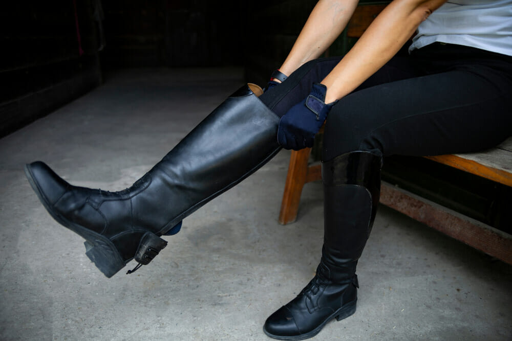 woman is putting riding boots on