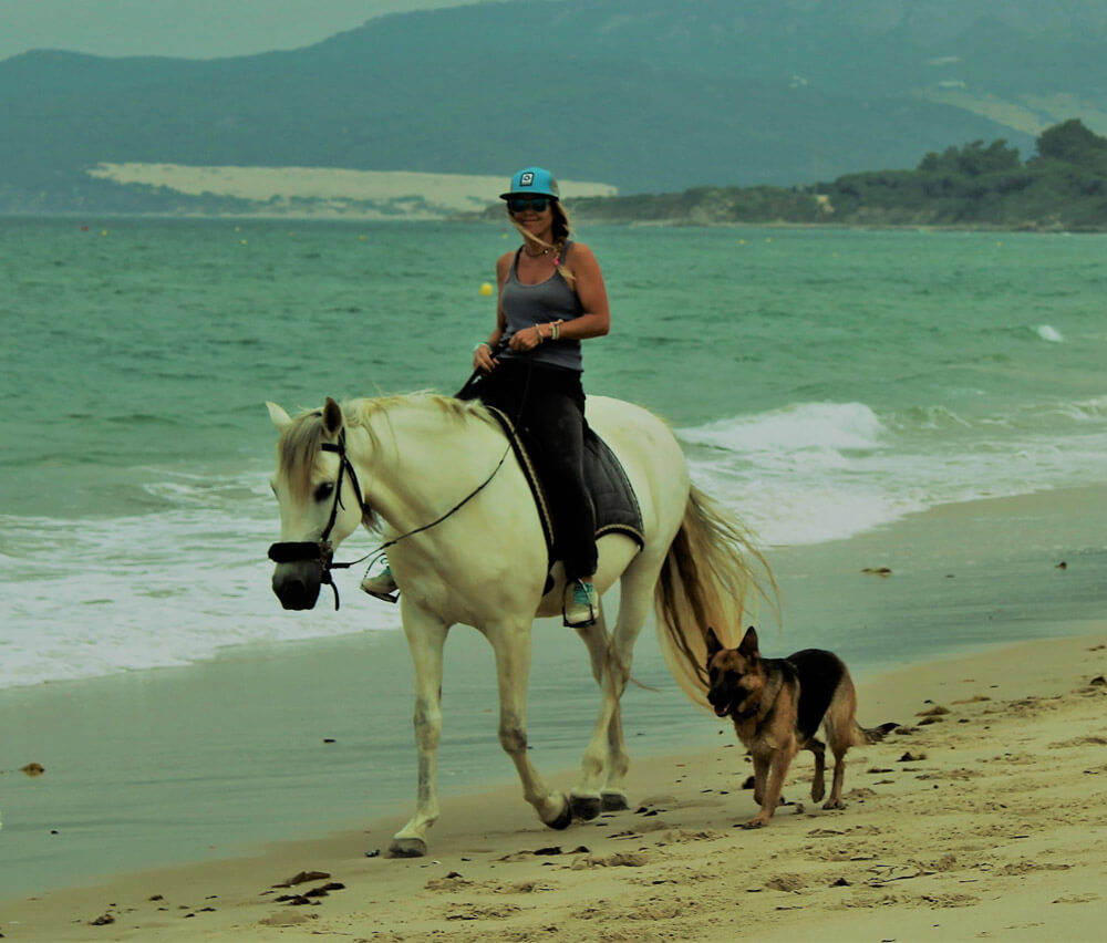 woman is riding on the beach with her dog