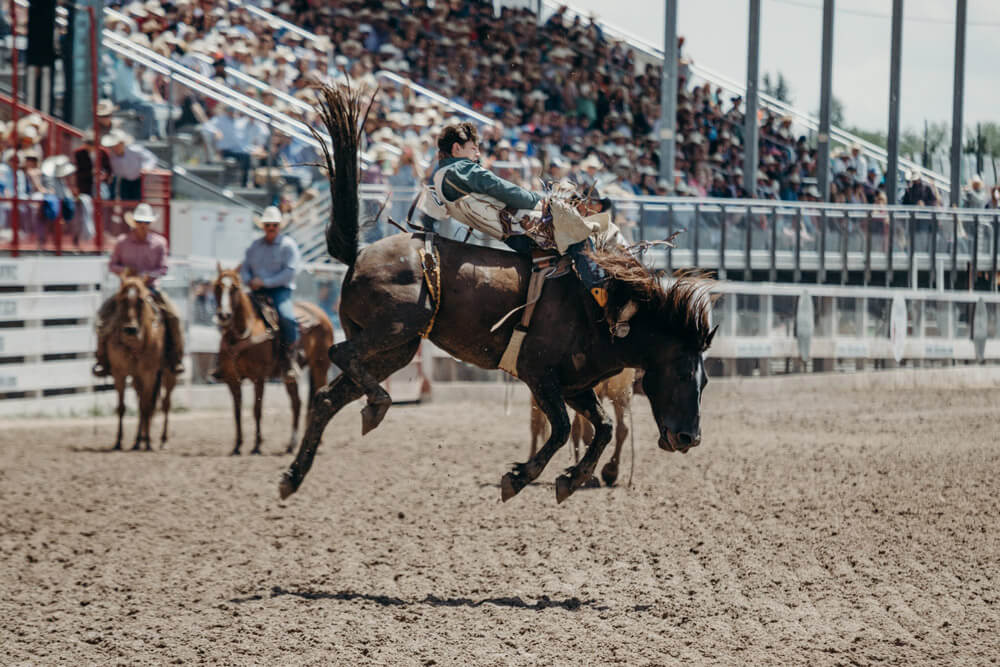 young man is performing on a rodeo